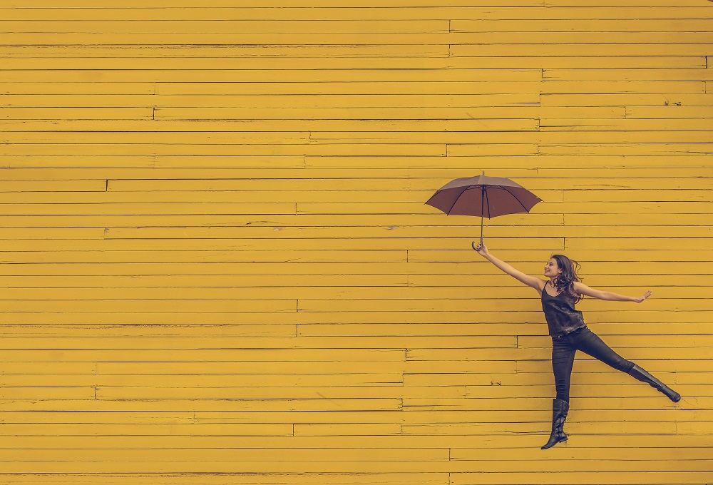 Woman floating in mid air against yellow painted background - learn how to build emotional resilience with Sarah Tuckett Psychotherapy and Counselling North Brisbane