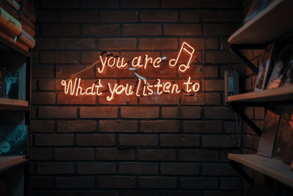 "Photo of neon sign saying ""You are what you listen to"". Learn how music can reduce your anxiety with Sarah Tuckett Psychotherapy and Counselling North Brisbane"