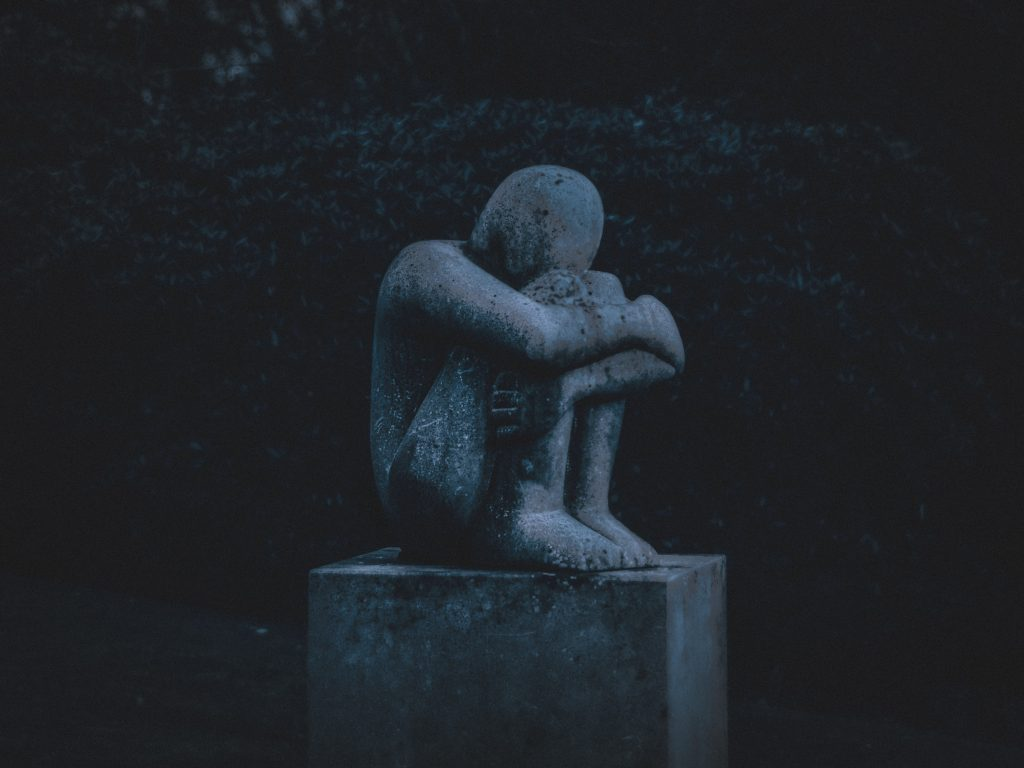 Grey stone statue of a person hugging their knees - learn about the link between chronic stress and depression with Sarah Tuckett Psychotherapy and Counselling, North Brisbane