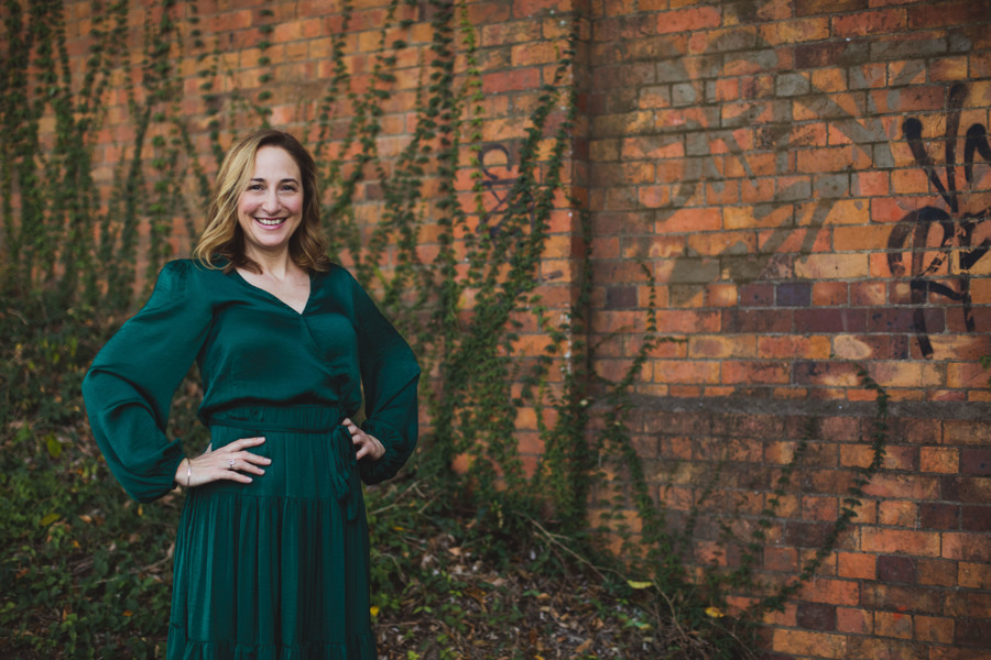 Image of Sarah Tuckett Psychotherapy and Counselling North Brisbane standing in a green dress against a brick wall covered in vines