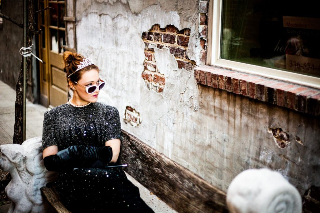 Woman sitting in bathtub in evening dress and tiara - finding your feminine power with Sarah Tuckett Psychotherapy and Counselling North Brisbane